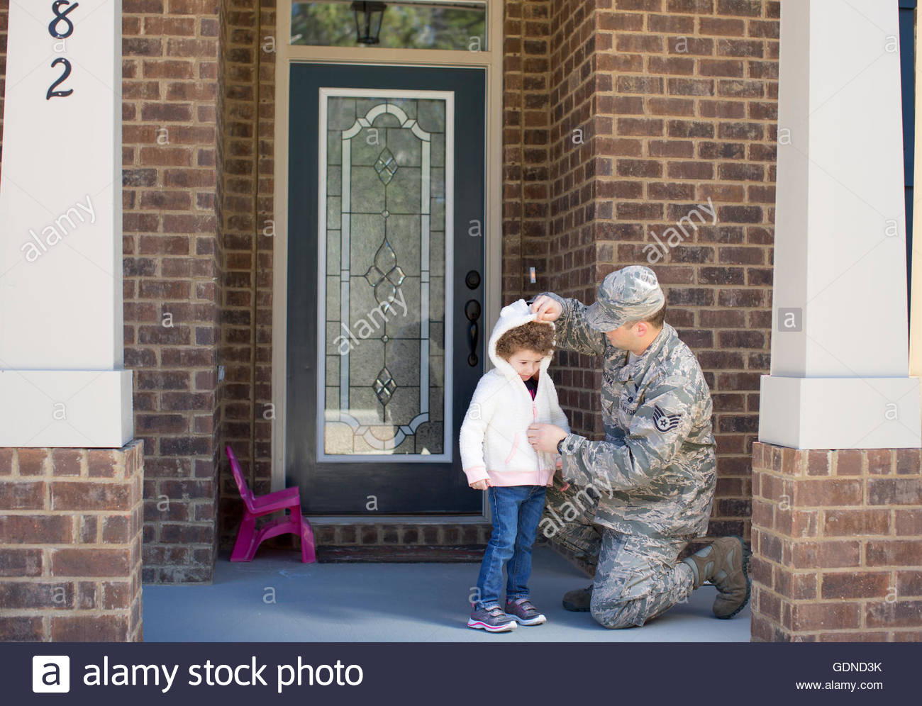 Male soldier with daughter at front door at air force military base - Stock Image