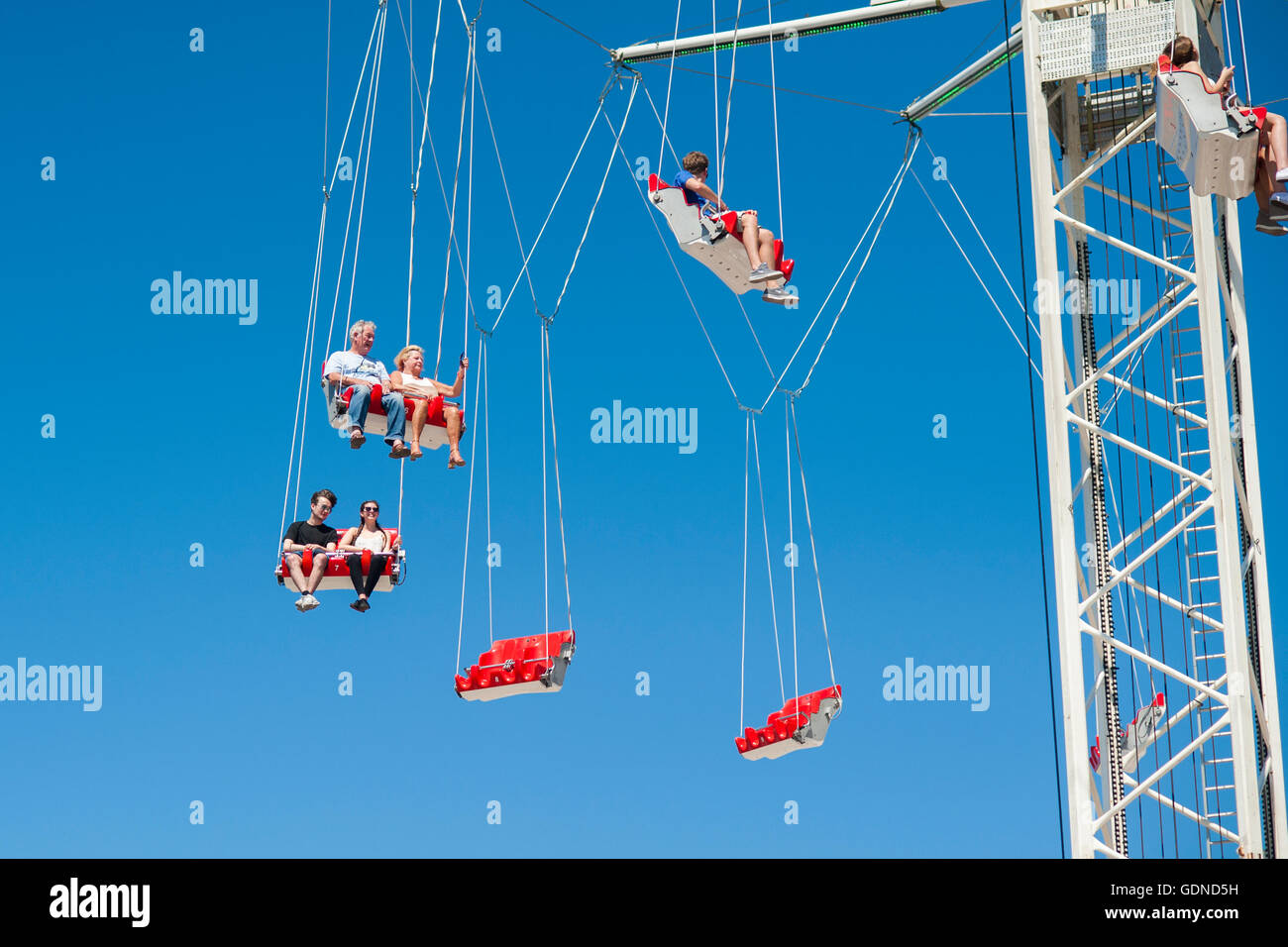 People on fairground ride swings high up in the air, UK - Stock Image