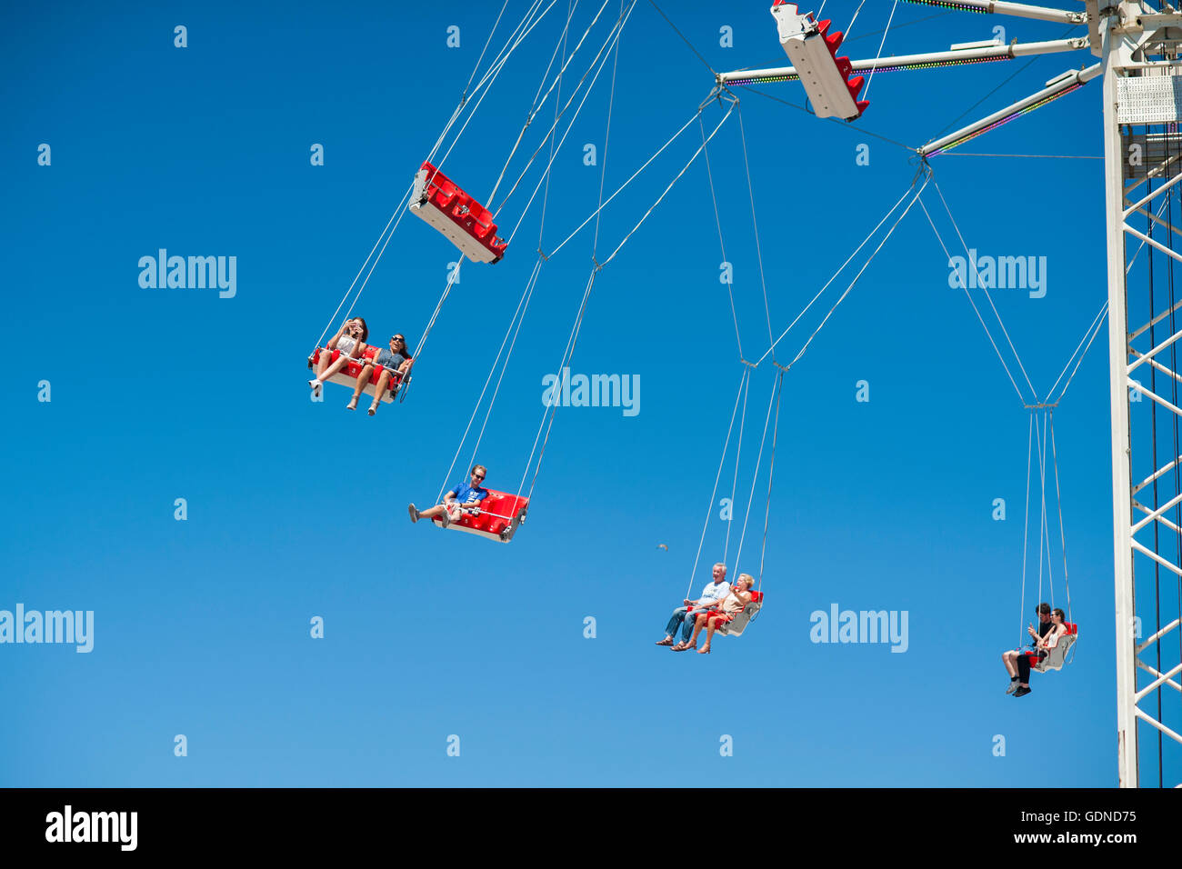 People on fairground ride swings high up in the air with  blue sky background - Stock Image