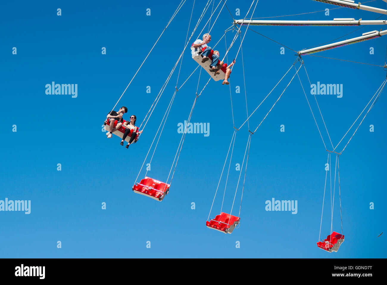 People on fairground ride swings high up in the air with a blue sky background - Stock Image