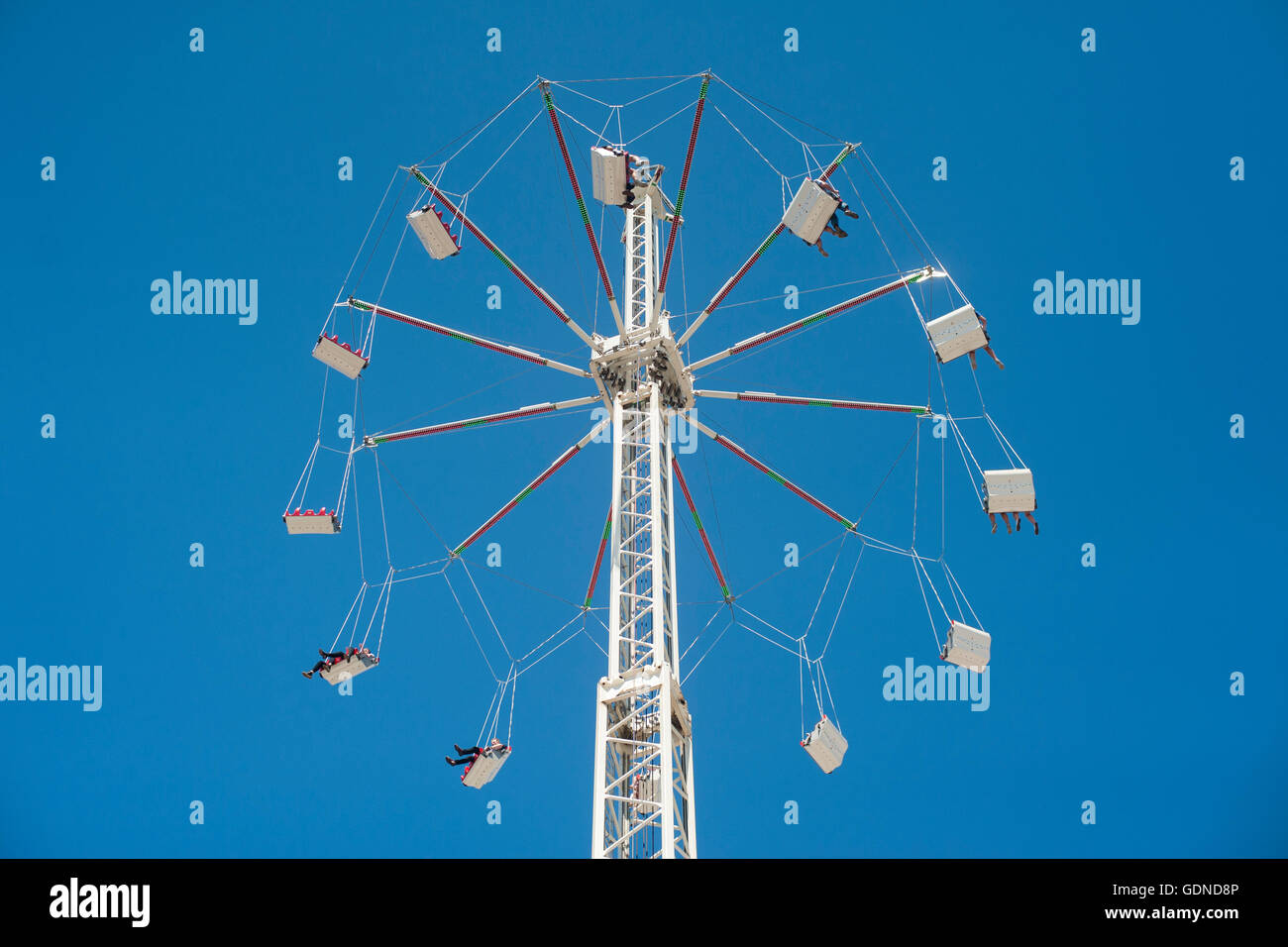 People on fairground ride swings high up in the air against a bright blue sky in summer 2016 - Stock Image