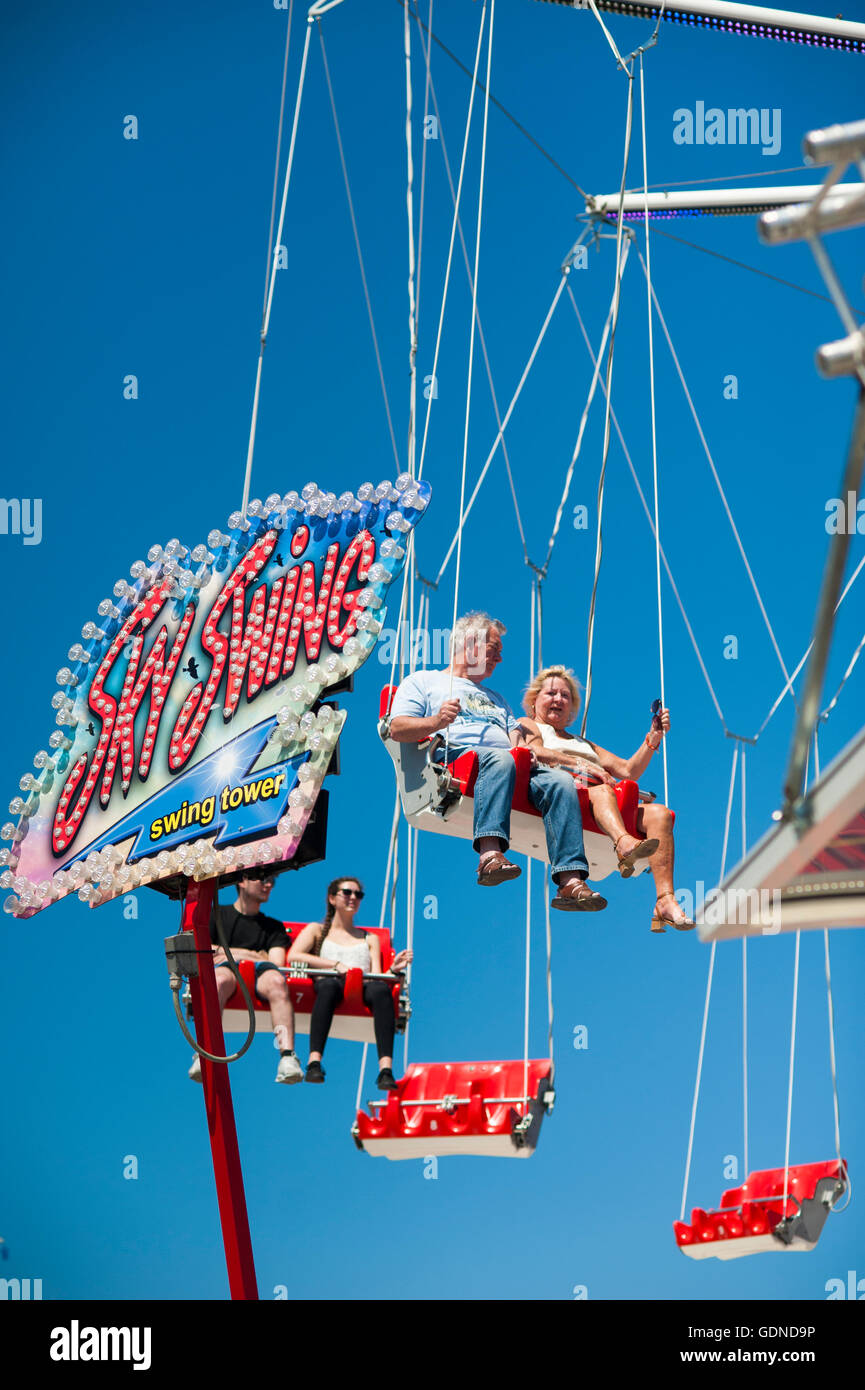 People on fairground ride swings high up in the air - Stock Image