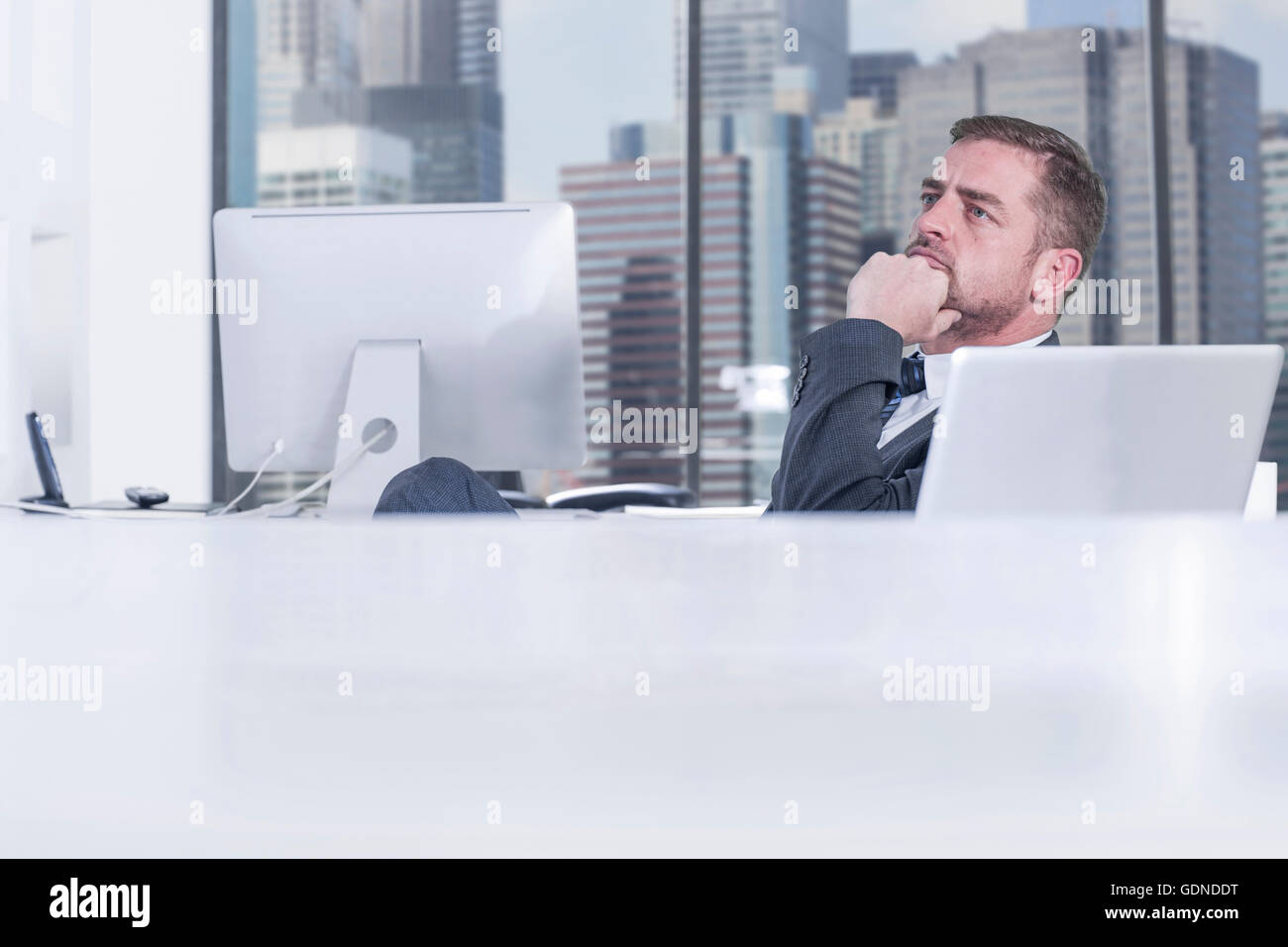 Businessman contemplating in front of computer - Stock Image