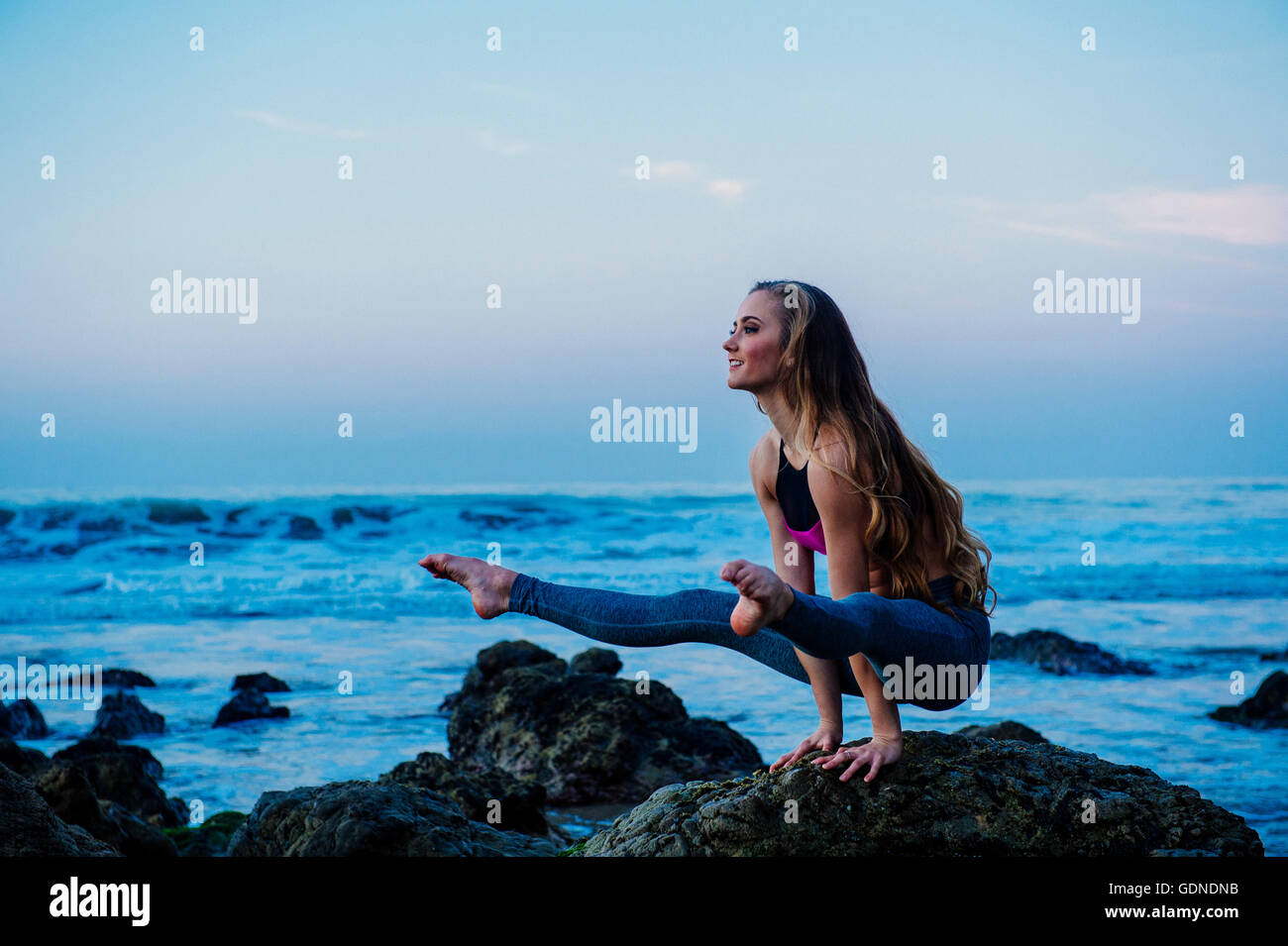 Young woman practicing yoga pose on rocks at beach, Los Angeles, California, USA Stock Photo
