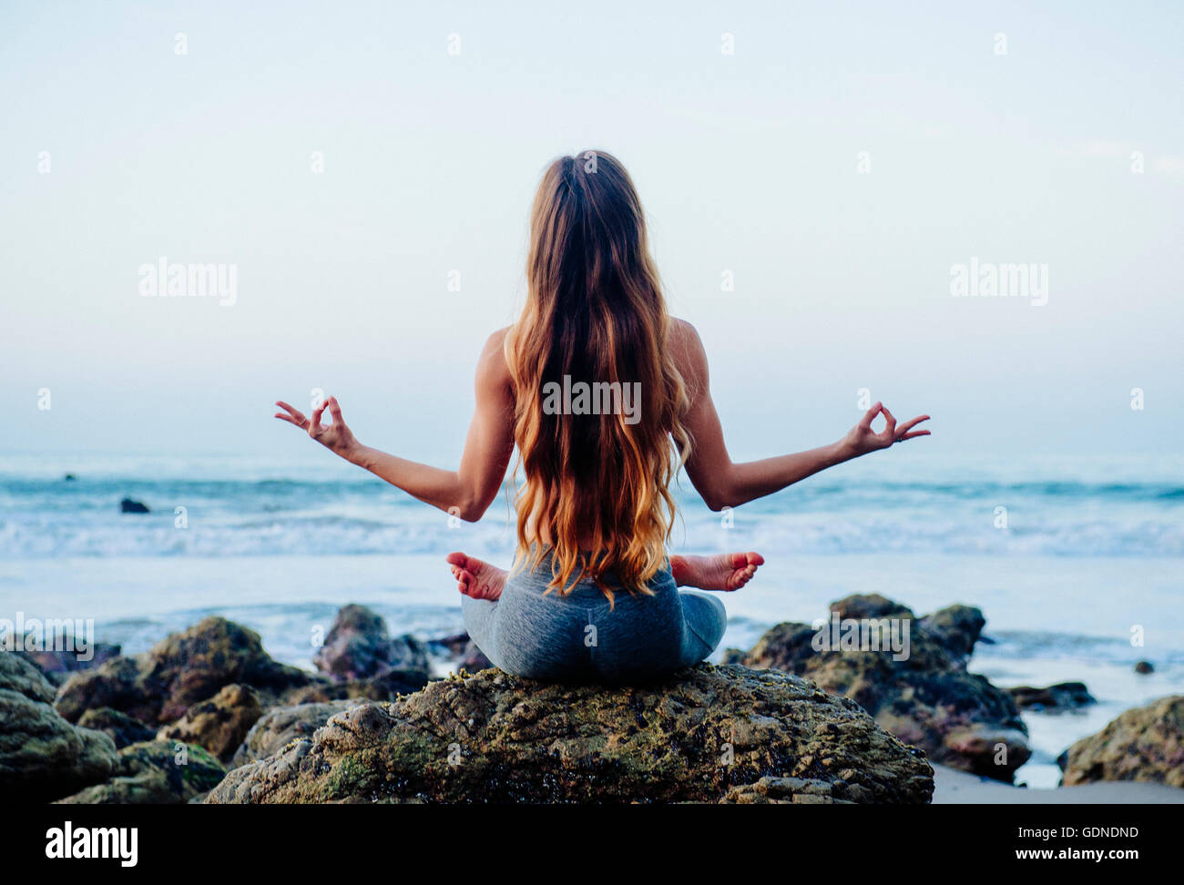 Rear view of young woman with long hair practicing lotus yoga pose on rocks at beach, Los Angeles, California, USA - Stock Image