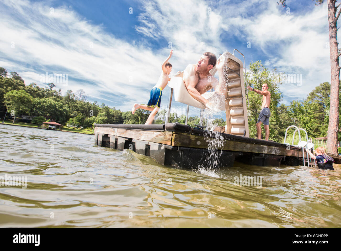 Man moving down head first on pier slide at Jackson Lake, Georgia, USA - Stock Image