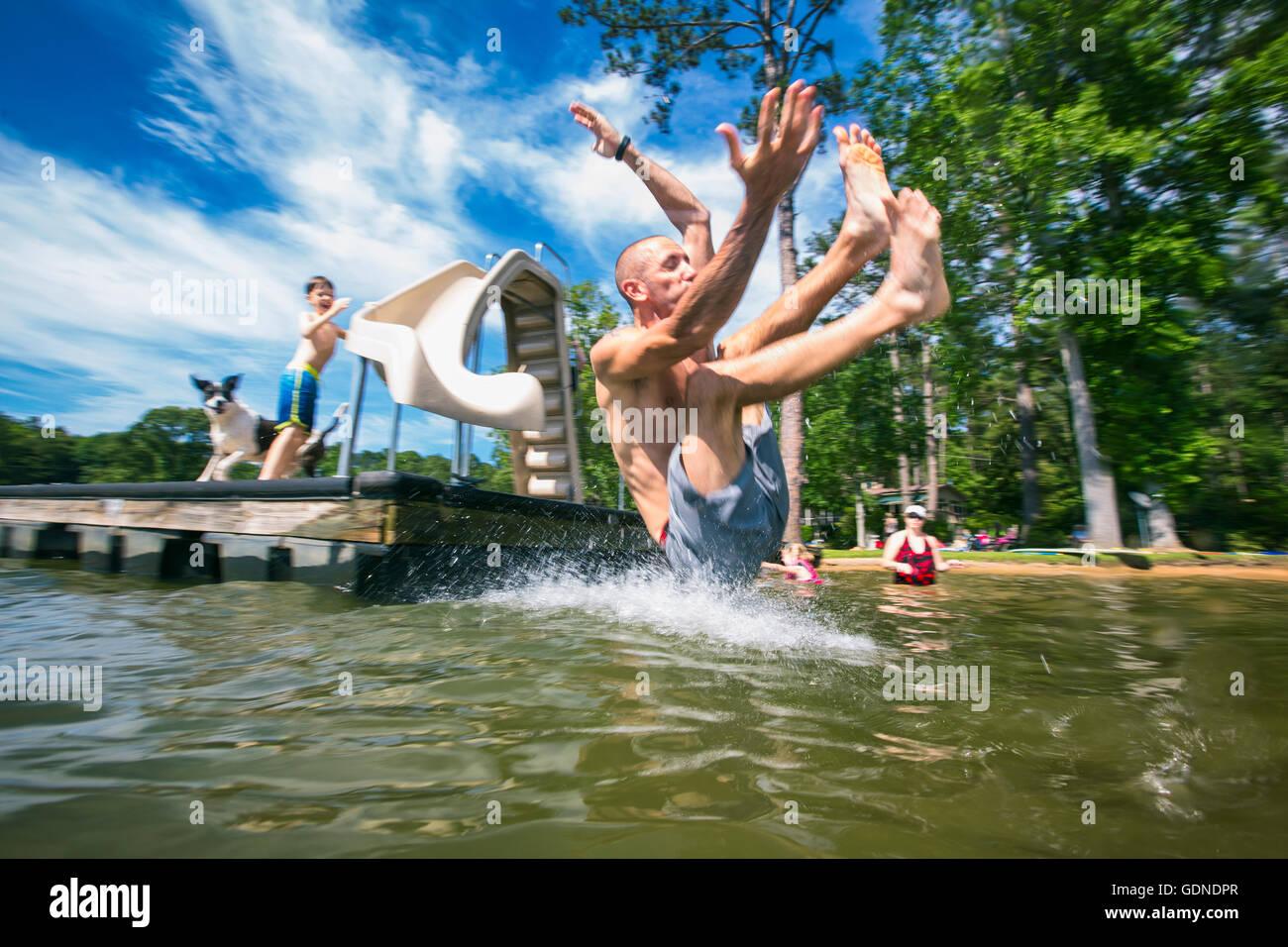 Man splashing into lake from pier slide at Jackson Lake, Georgia, USA - Stock Image