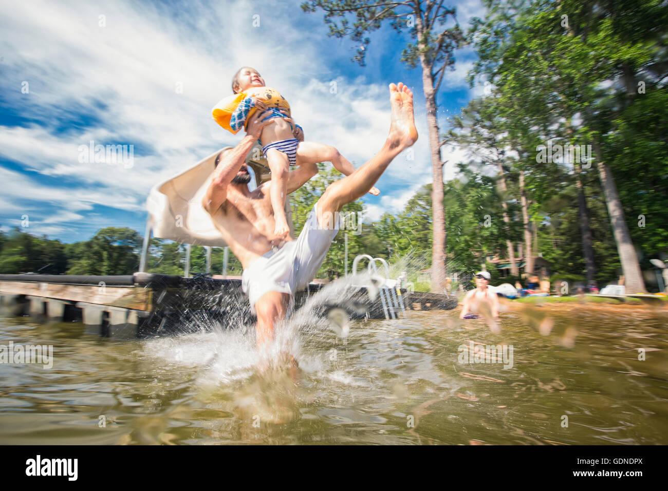 Man holding up daughter jumping from slide at Jackson Lake, Georgia, USA - Stock Image