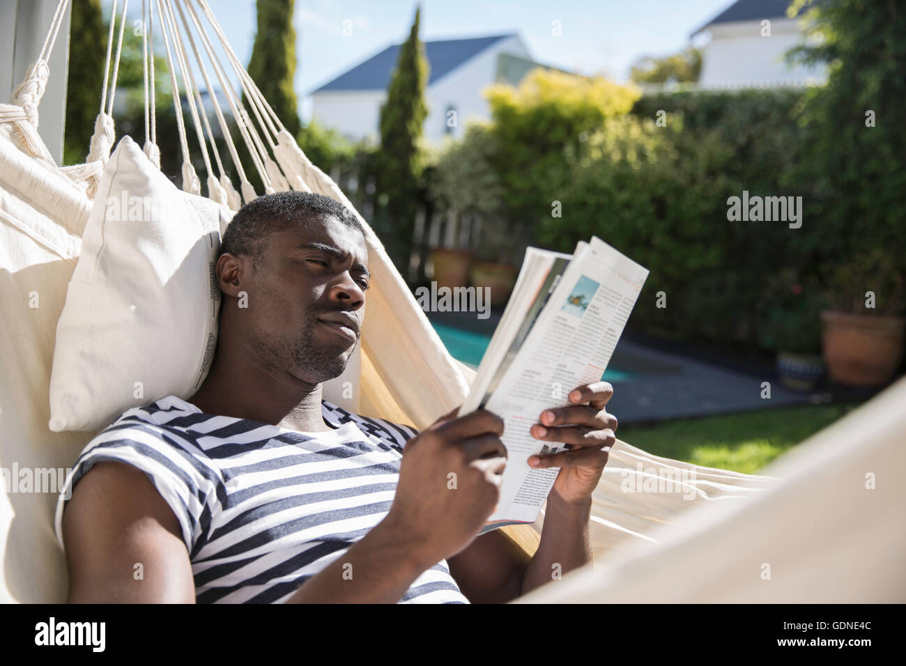 Young man reclining on garden hammock reading a magazine - Stock Image