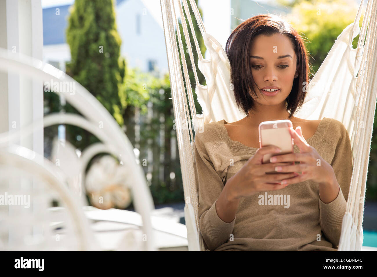 Young woman relaxing on garden hammock reading smartphone texts - Stock Image