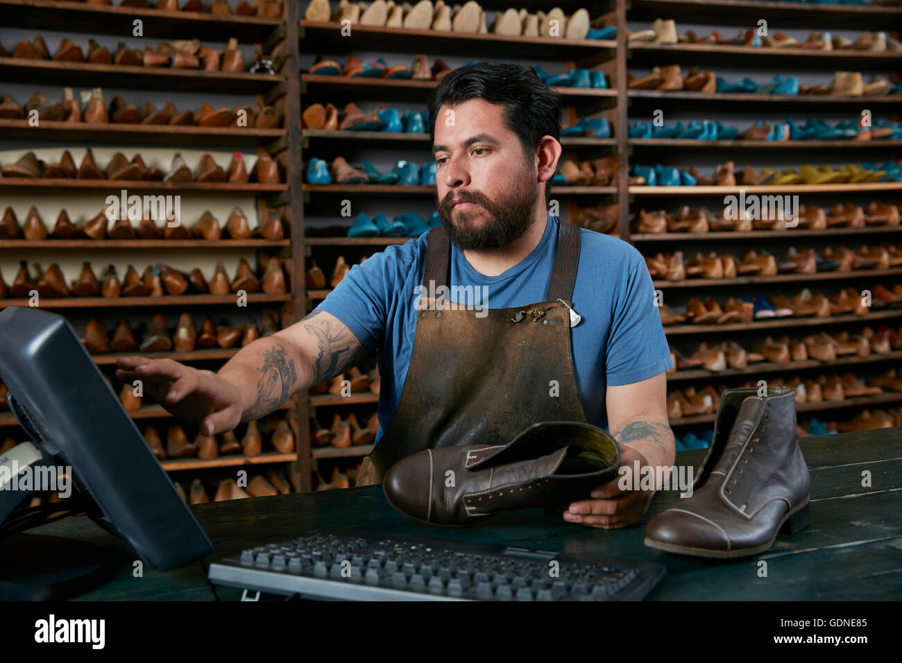 Male cobbler making invoice for boots in traditional shoe shop - Stock Image