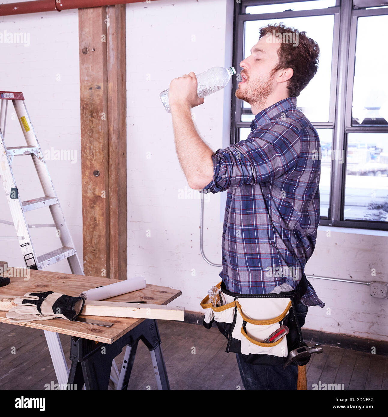 Carpenter in workshop drinking from water bottle - Stock Image
