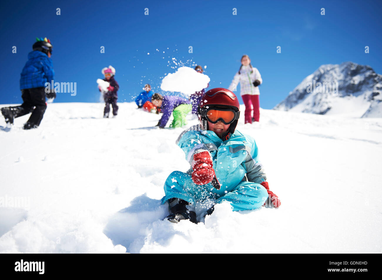 Young boy throwing snowball whilst friends play behind him - Stock Image