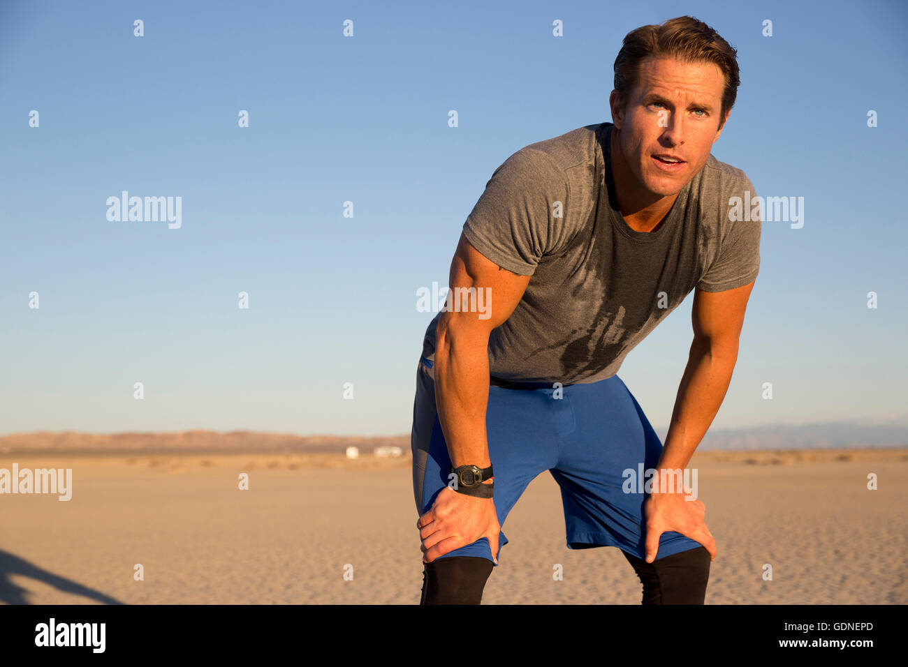 Man training, sweating and leaning forward on dry lake bed, El Mirage, California, USA - Stock Image