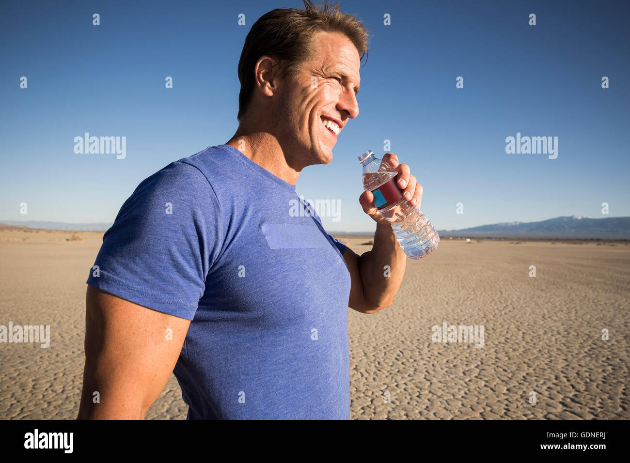 Man training, with bottled water on dry lake bed, El Mirage, California, USA - Stock Image