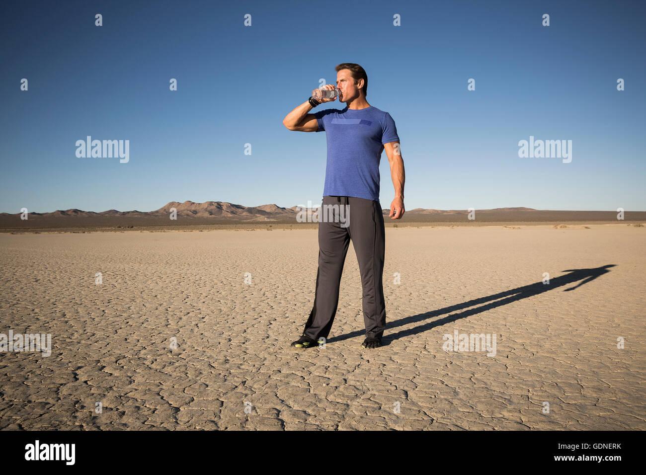Man training, drinking bottled water on dry lake bed, El Mirage, California, USA - Stock Image
