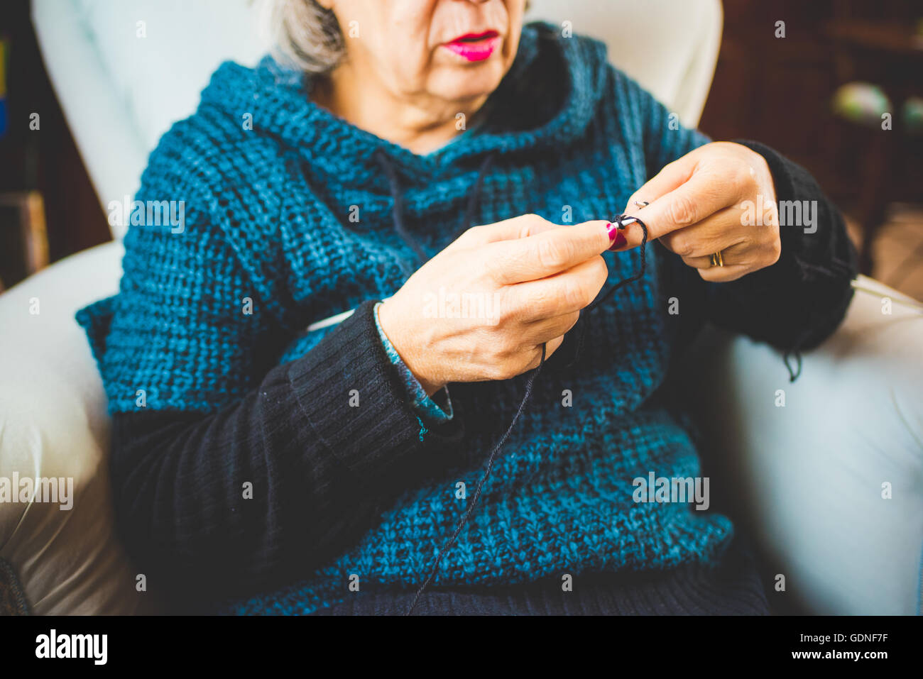 Hands of a woman knitting with knitting needles and woolen yarn, filtered vintage - handcraft, hobby concept - Stock Image