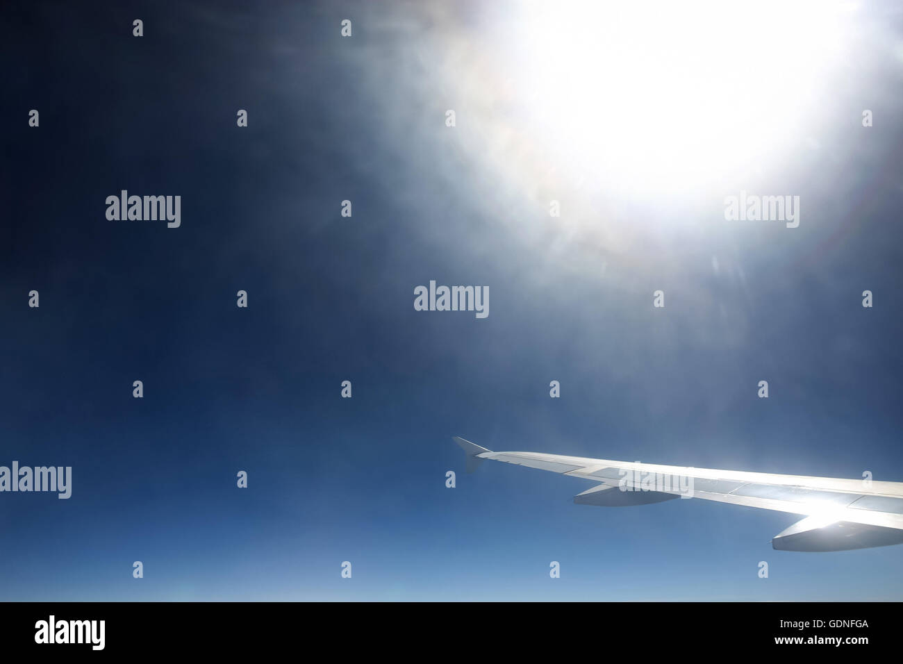 A view of the airplane wing and sunlight from the airplane. - Stock Image