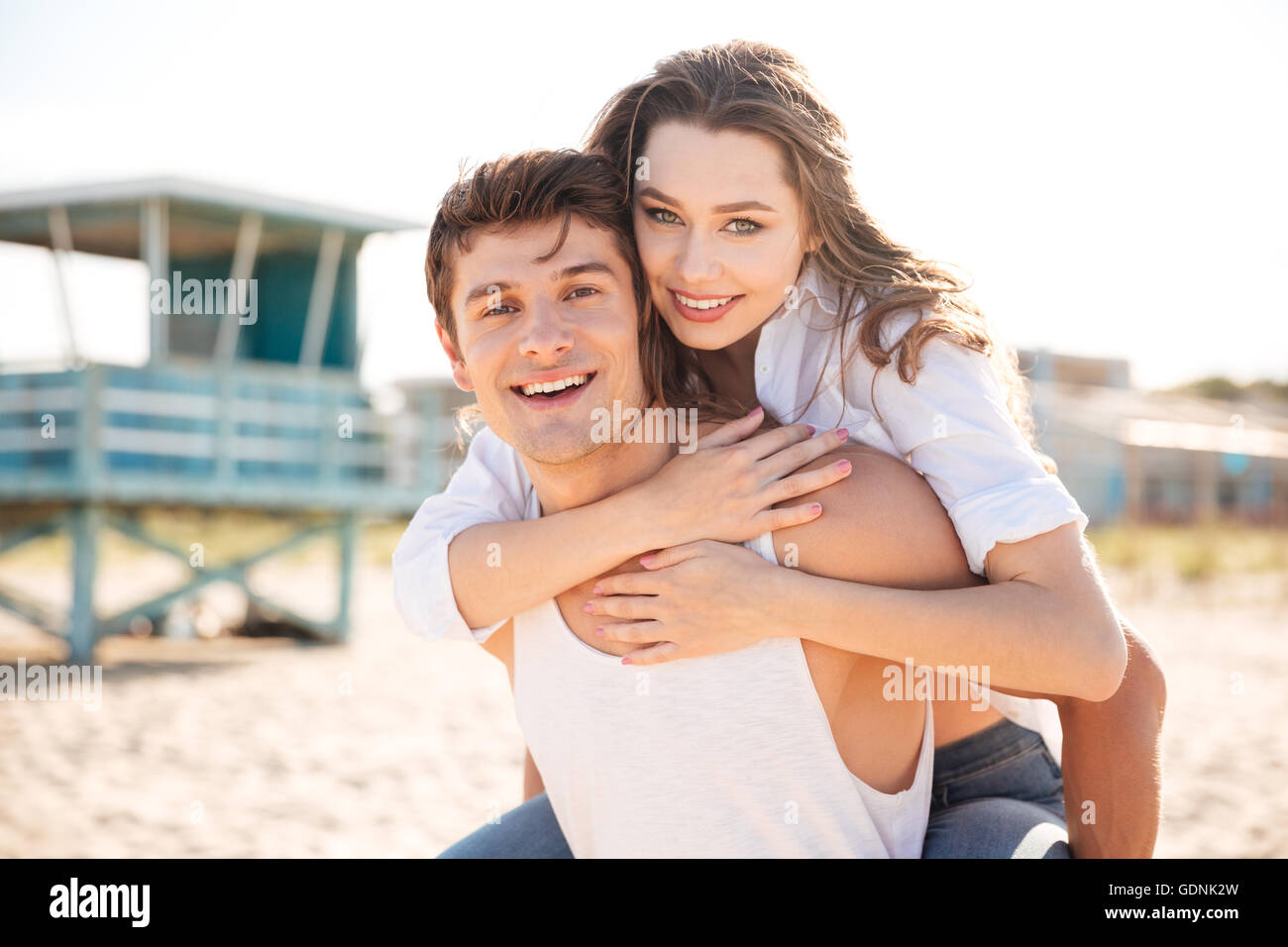 Portrait of cheerful young man piggybacking his girlfriend on the beach - Stock Image