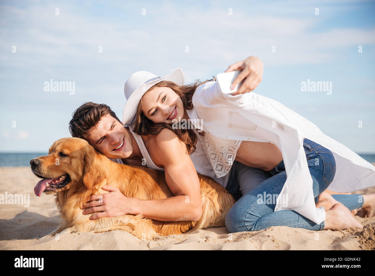 Smiling young couple with dog talking selfie with smartphone on the beach - Stock Image