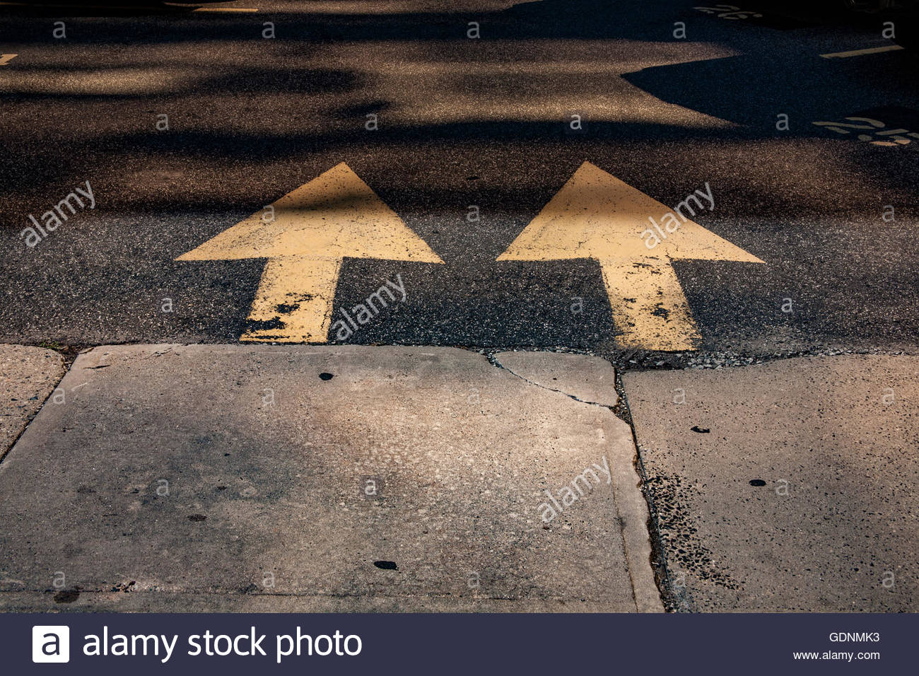 Side by side identical traffic arrows in a parking lot. - Stock Image