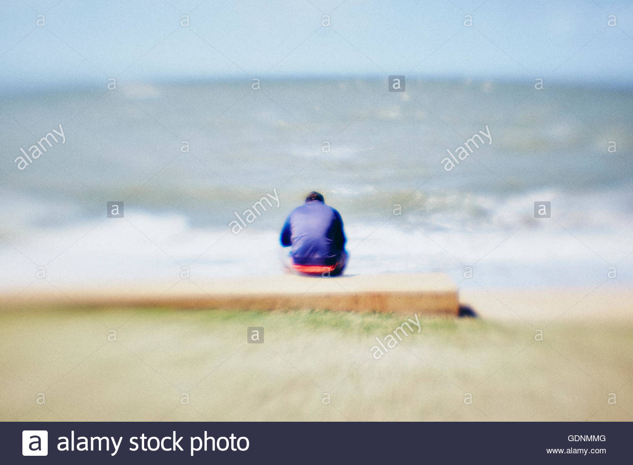 young male, back to camera, sitting hunched, looking out to sea - Stock Image