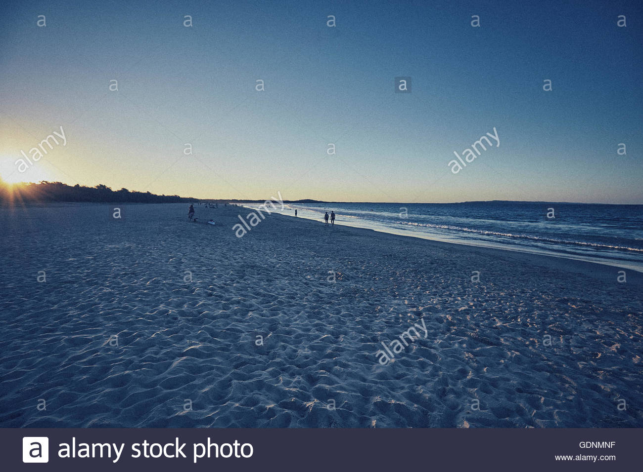 small groups of people on a quiet beach at sunset - Stock Image