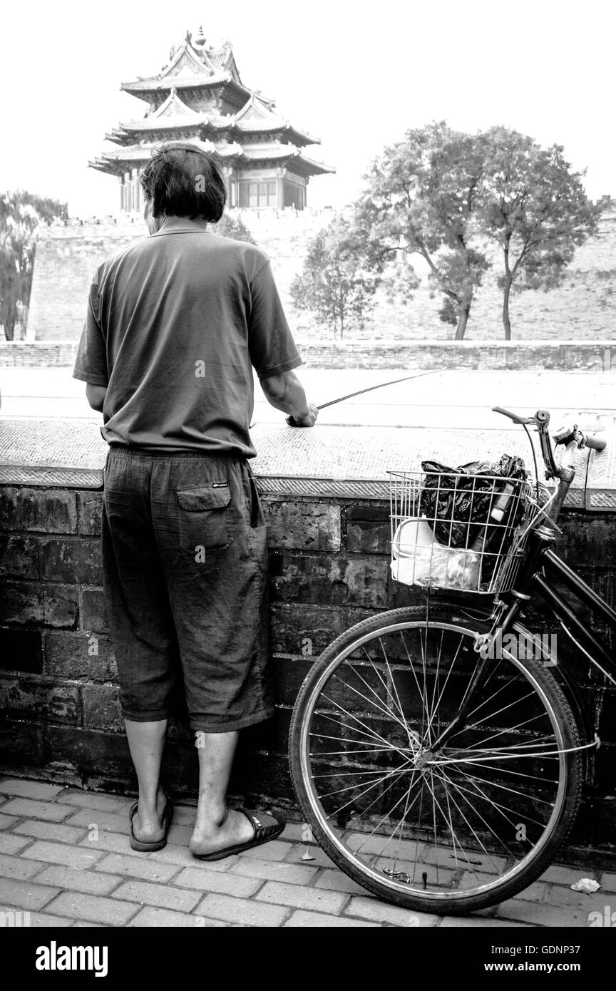 Rear View of Man Fishing With a Pole At Forbidden City Outside Canal - Stock Image