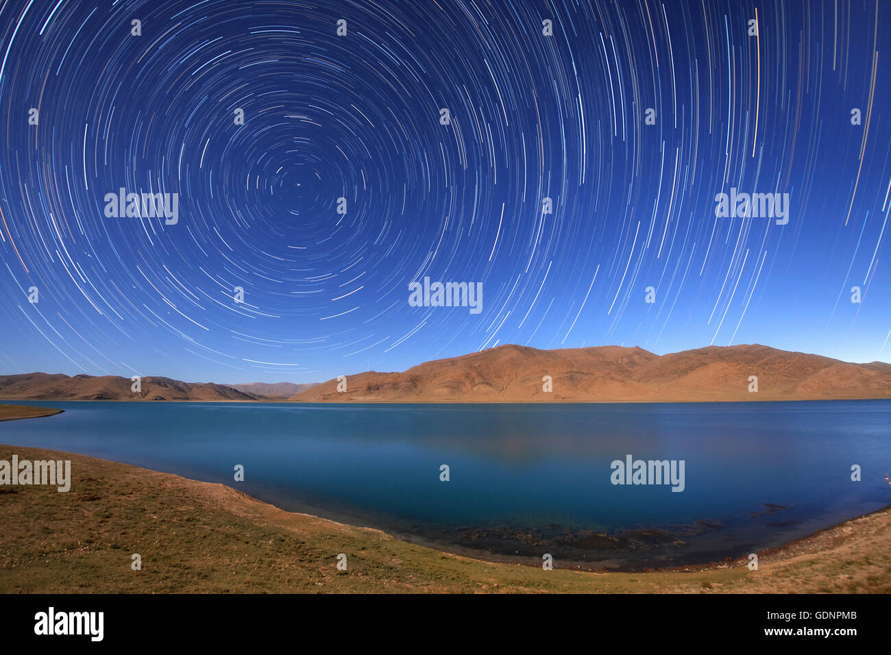 Star trails around the northern celestial pole over Yamdrok Lake, Tibet, China. - Stock Image