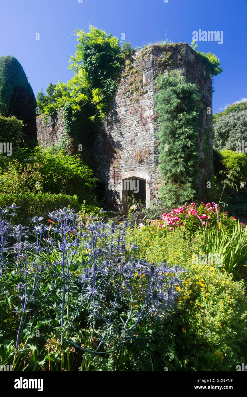 The stone tower in the walled garden at the Garden House, Devon, UK nestles amongst rich shrub and perennial planting - Stock Image