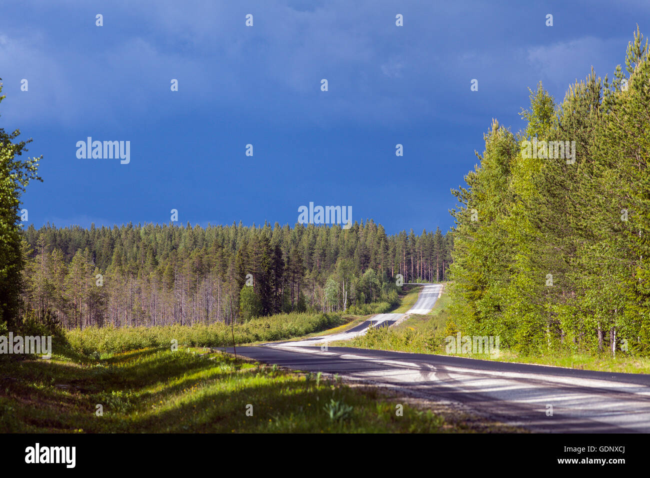 Country road in rural countryside. Heavy showers in the background. - Stock Image