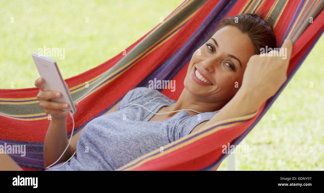 Happy young woman listening to music in a hammock - Stock Image
