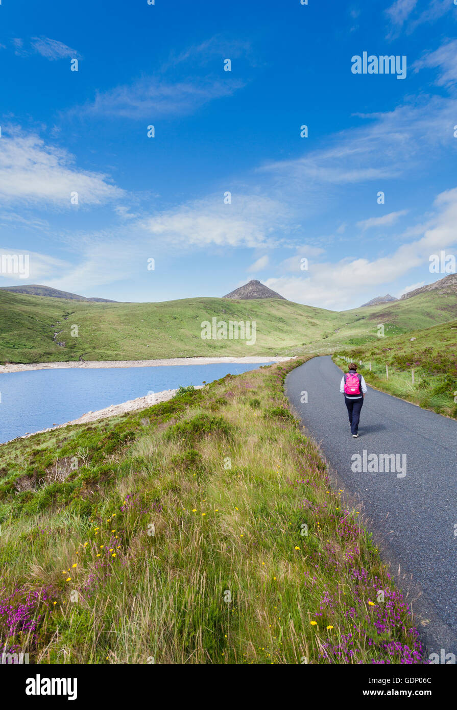 Lone woman walking on pathway beside the Silent Valley Reservoir, Mourne Mountains, Down, Norethern Ireland - Stock Image