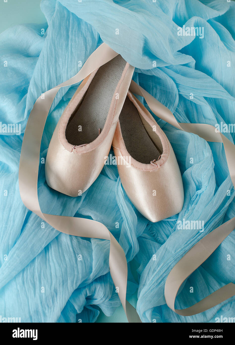 A pair of pointe shoes on light blue fabric background - Stock Image