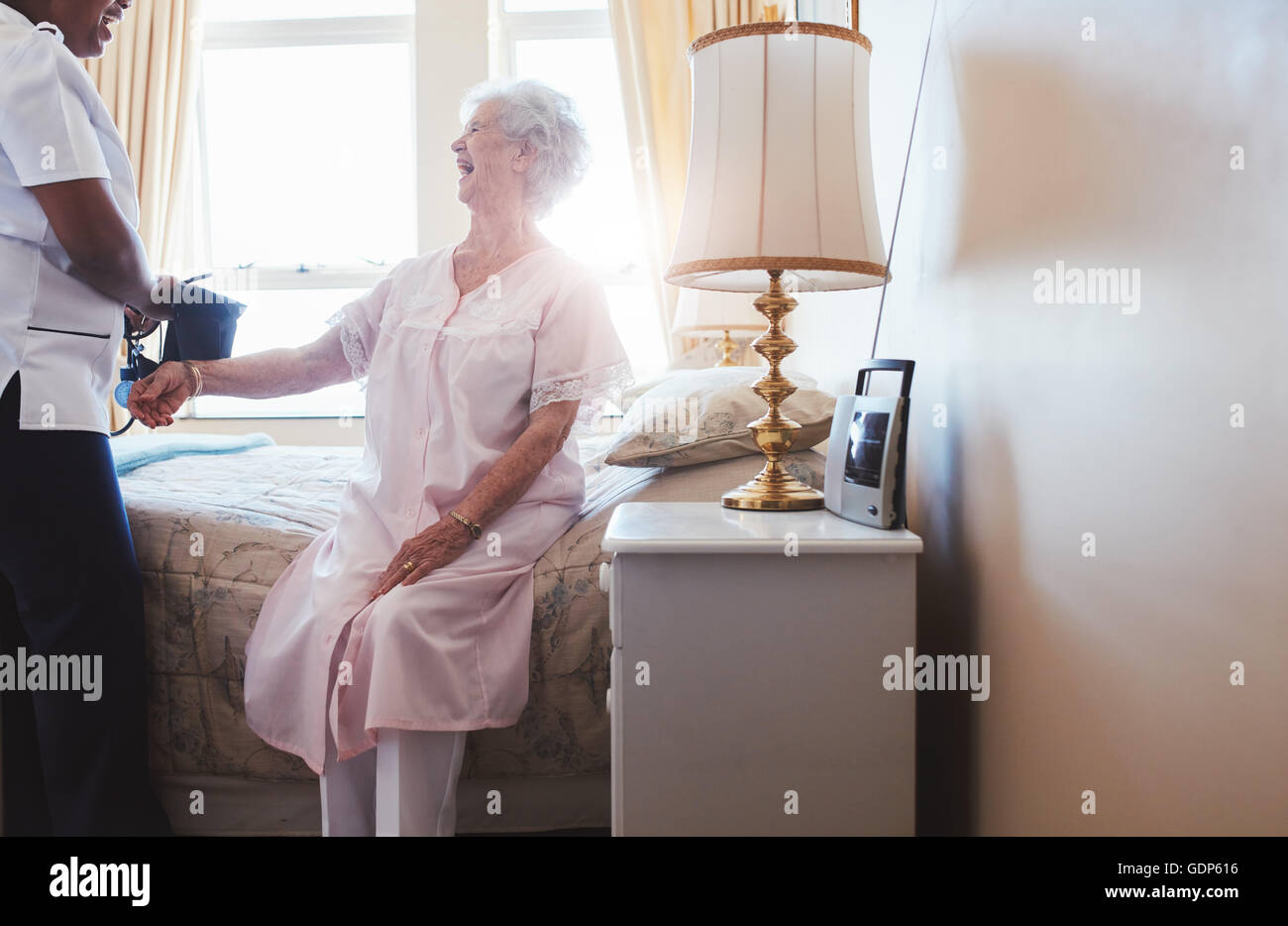 Indoors shot of happy senior woman sitting on bed with female nurse checking blood pressure. Home caregiver testing - Stock Image