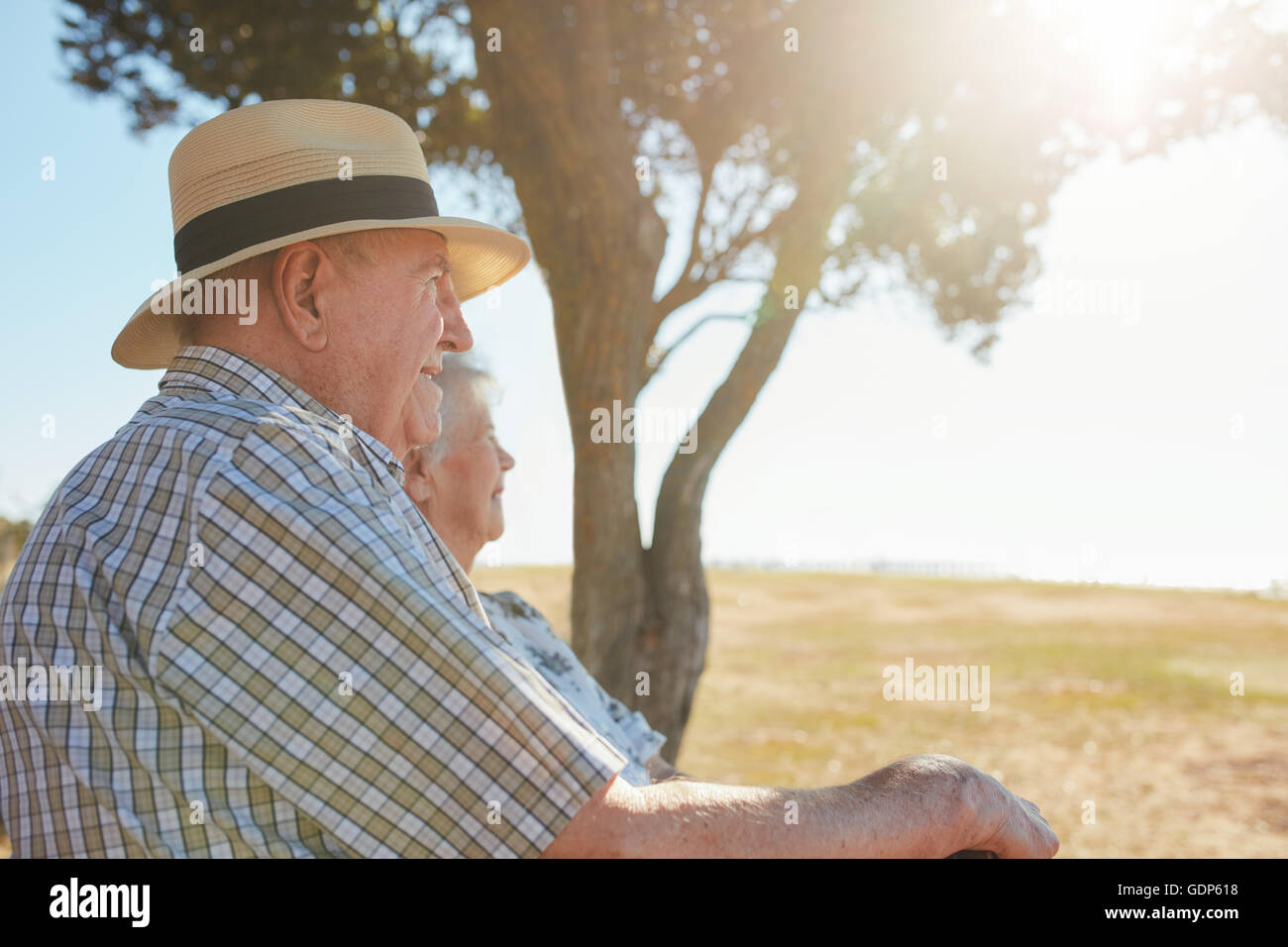 Side view shot of senior man in hat sitting outdoors with his wife and enjoying a view. Elderly couple relaxing - Stock Image
