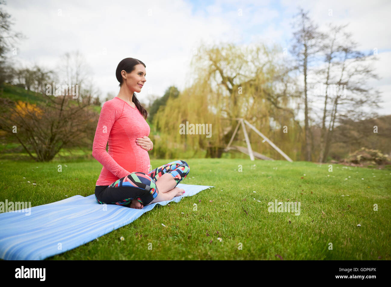 Pregnant woman sitting outdoors, holding belly - Stock Image