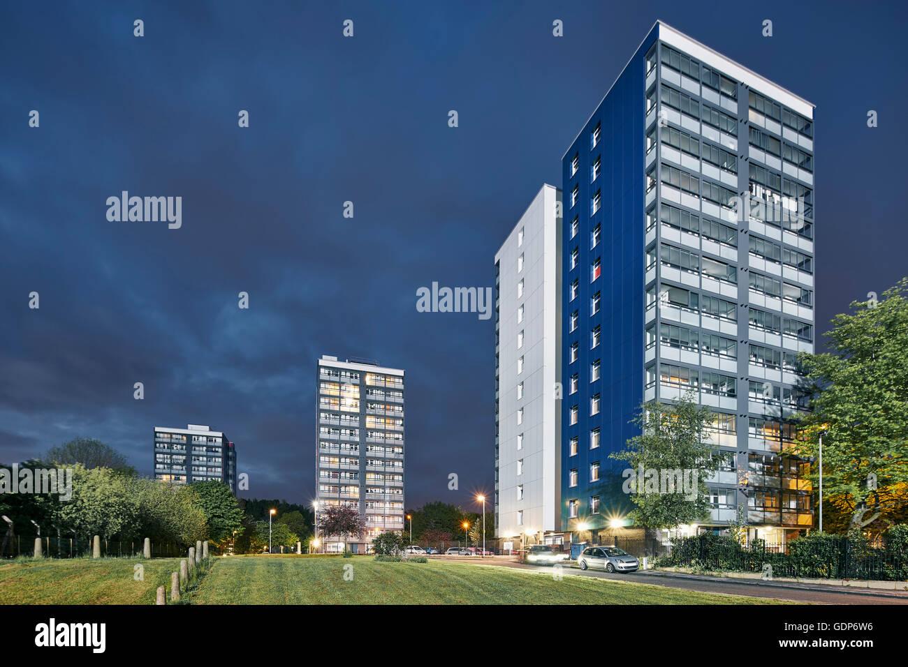 Three urban public housing apartment blocks at night - Stock Image