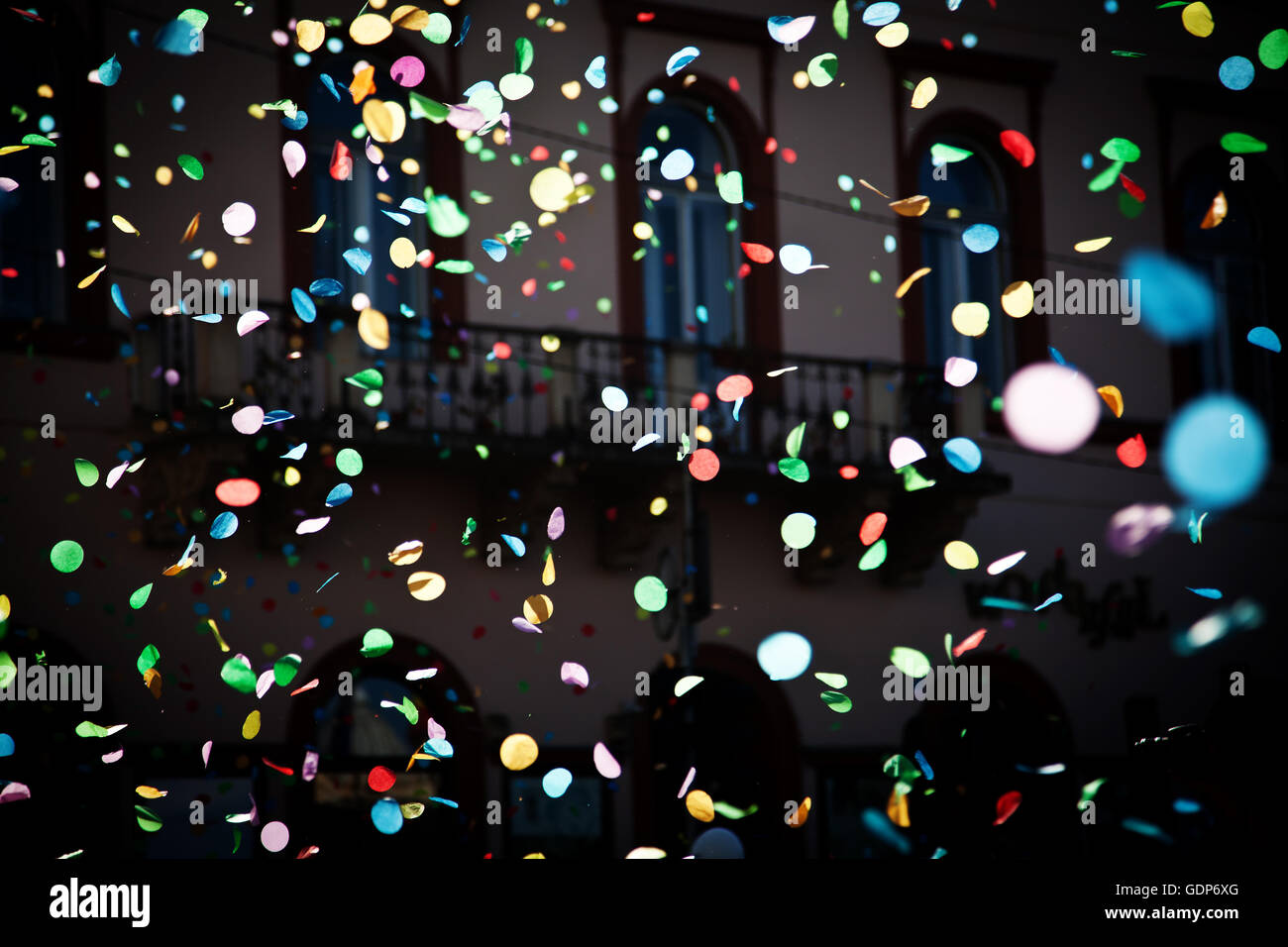 falling confetti in the city festival on blue sky background - Stock Image
