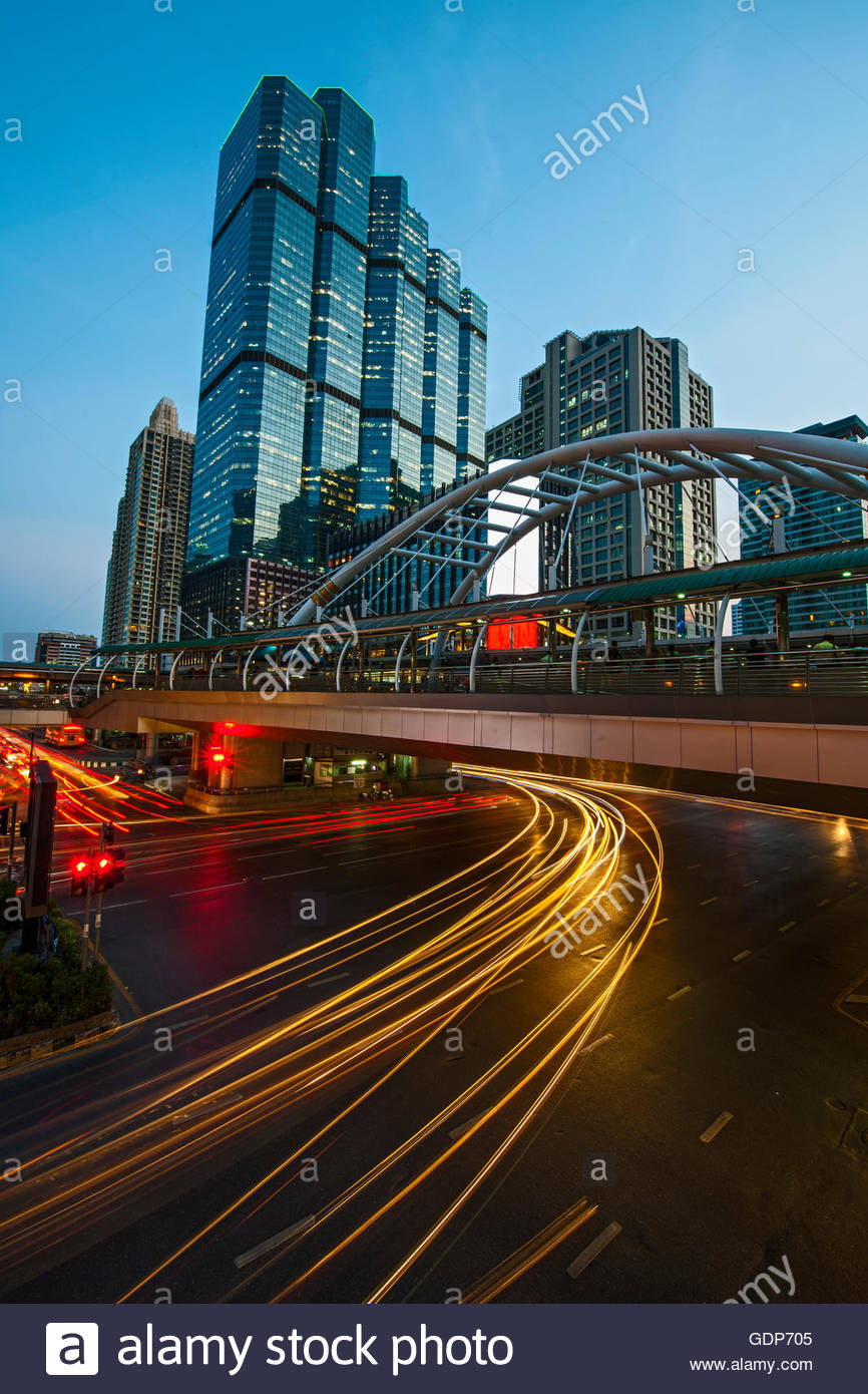 Light trails on road below footbridge, Sathorn, Bangkok, Thailand - Stock Image