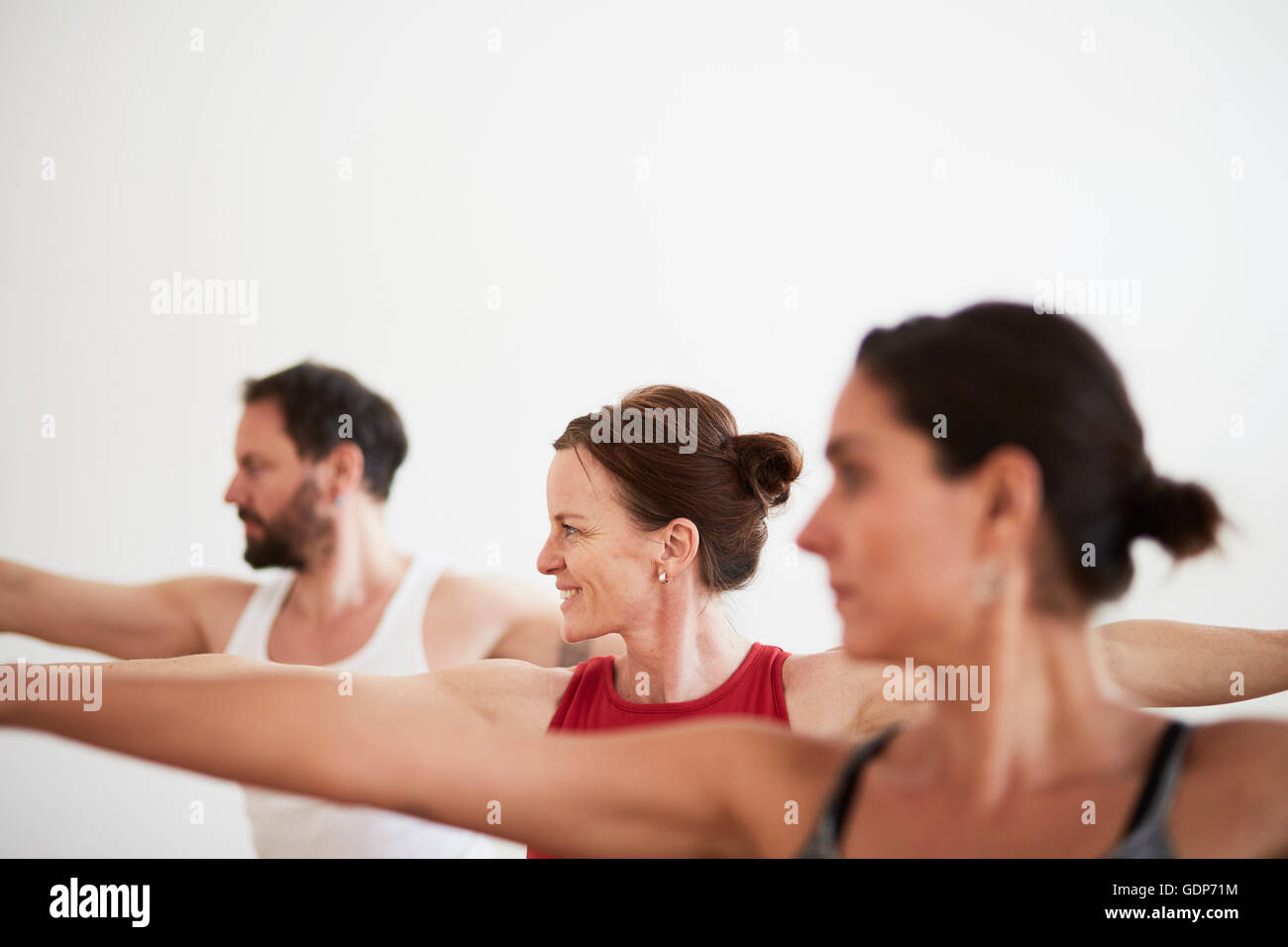 People in exercise studio arms open in yoga position - Stock Image