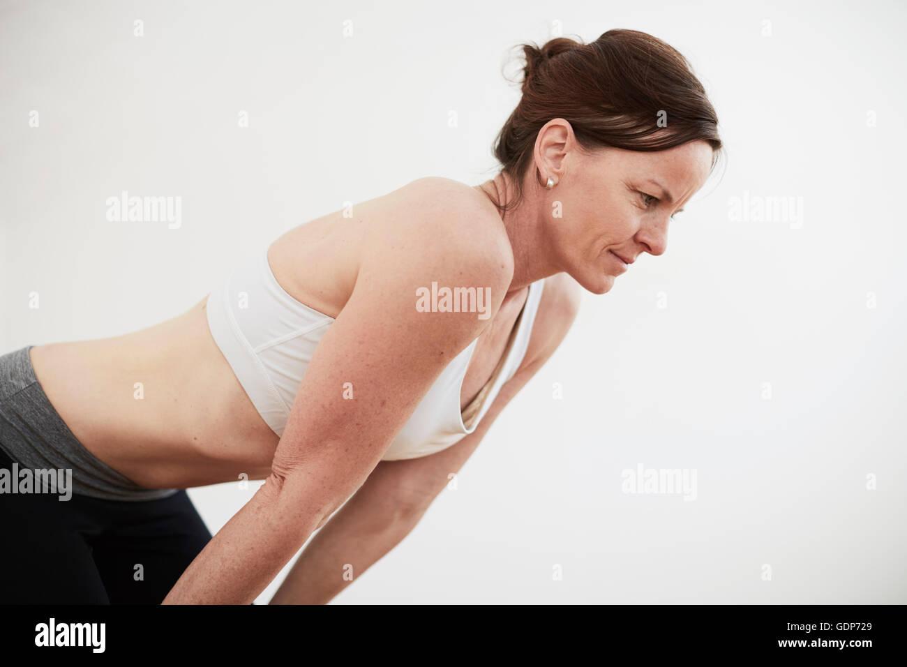 Woman in exercise studio wearing crop top bending forward - Stock Image