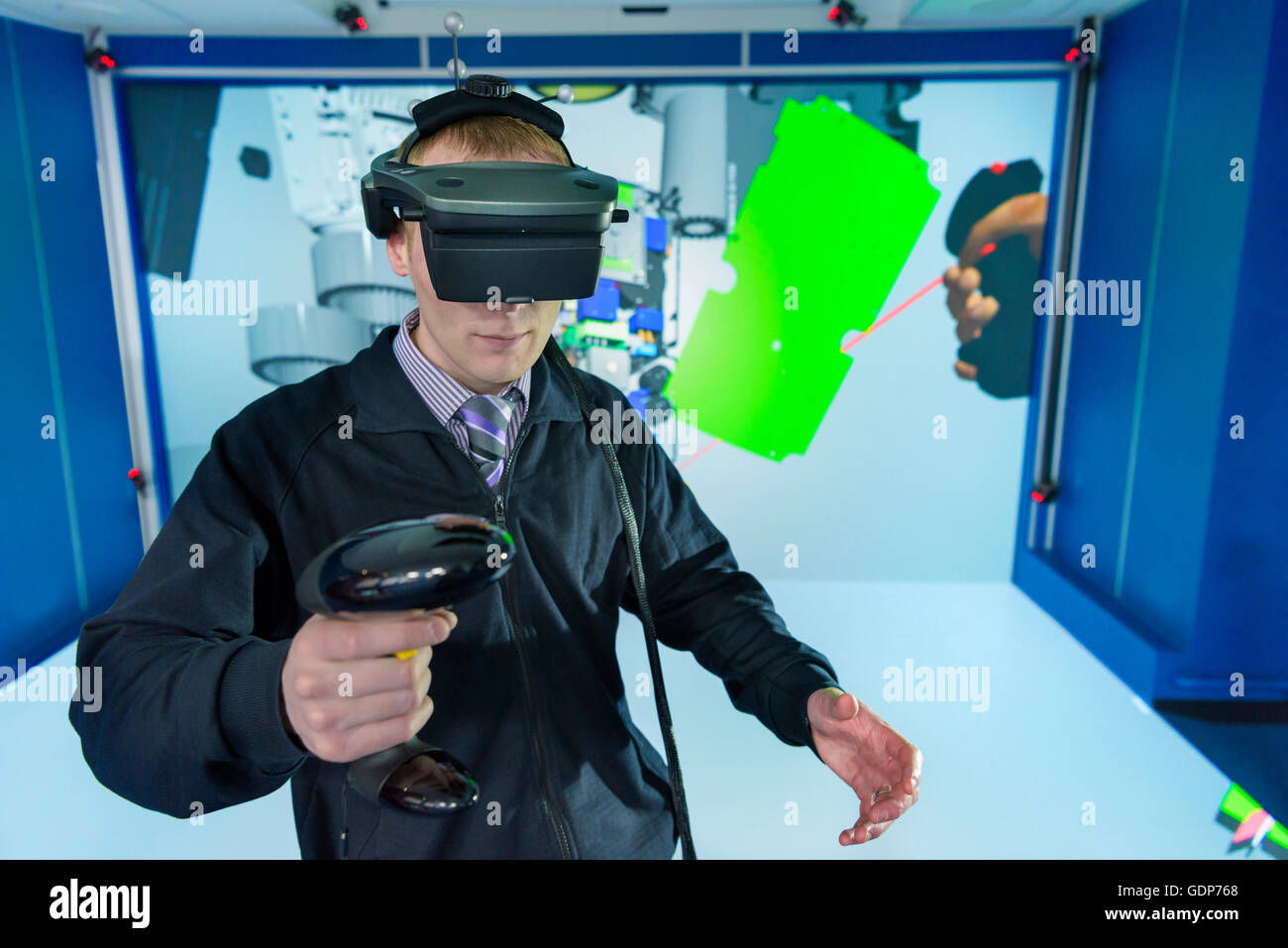 Engineer wearing VR headset in virtual reality suite - Stock Image