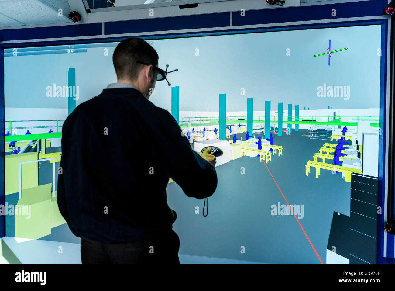 Engineer inspecting factory layout in 3D in virtual reality suite - Stock Image