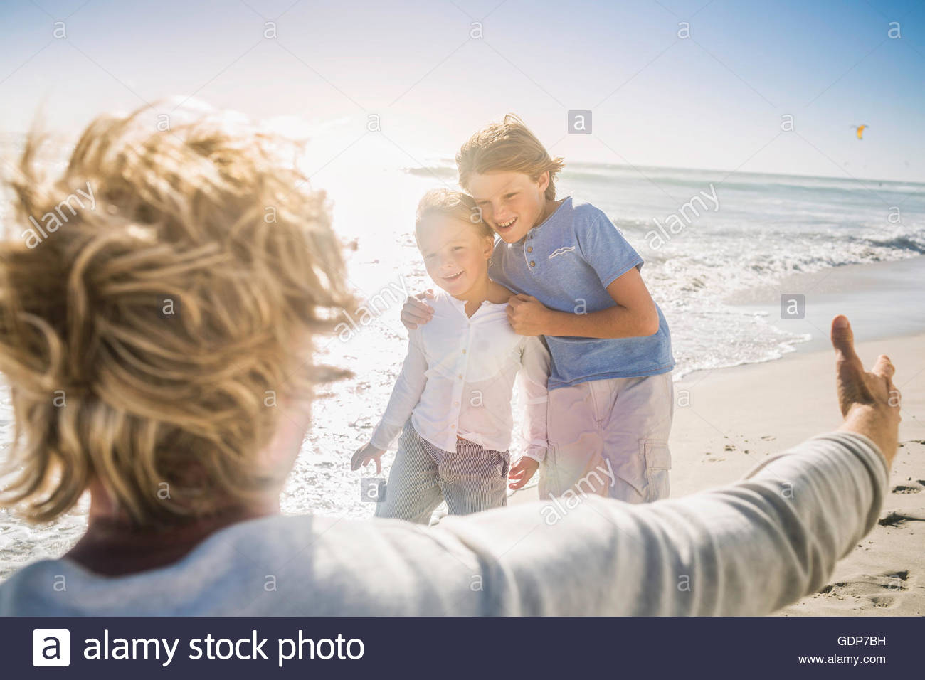 Father opening arms to sons on beach - Stock Image