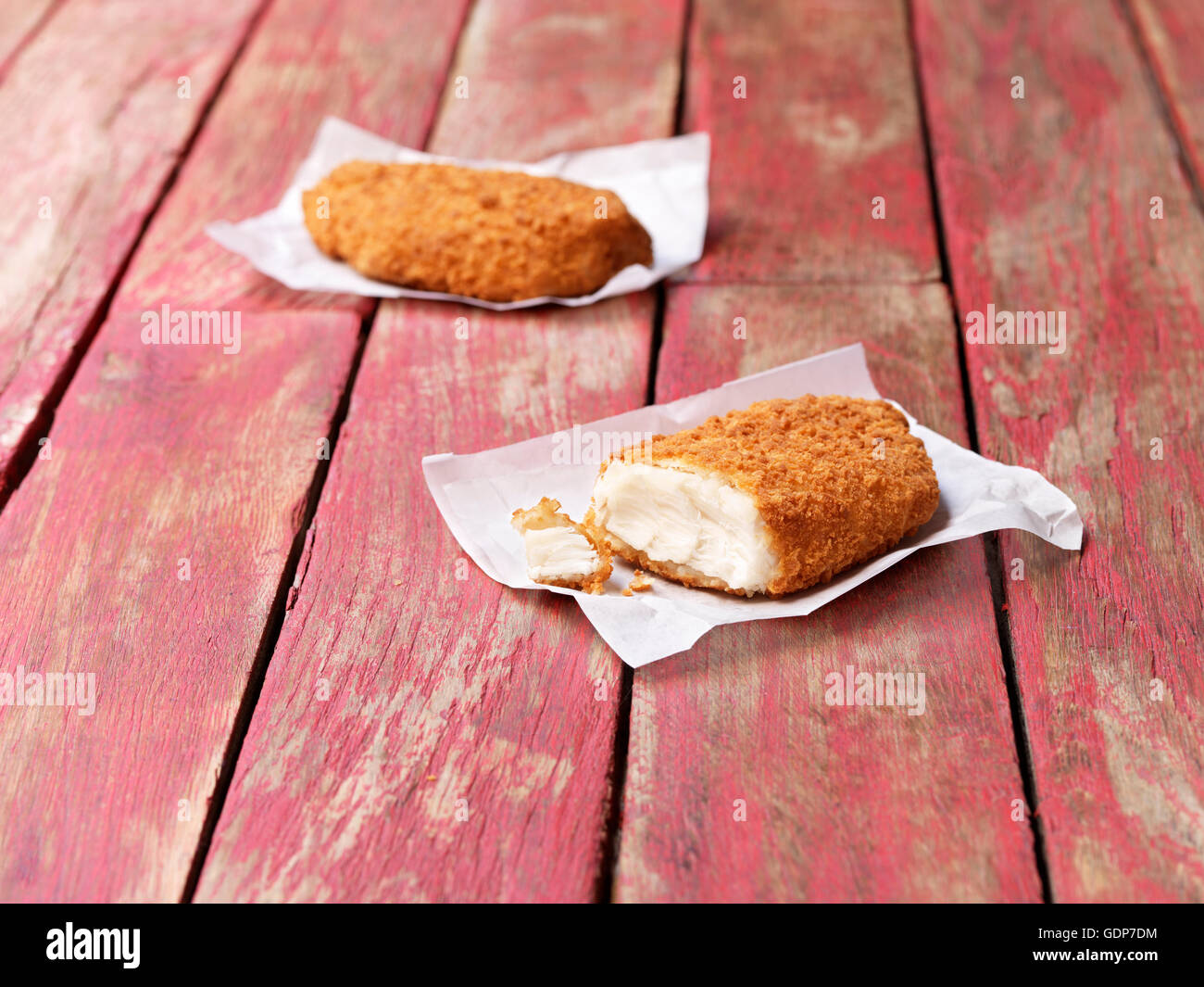 Food, fish, gluten free breaded cod on painted red wooden table - Stock Image