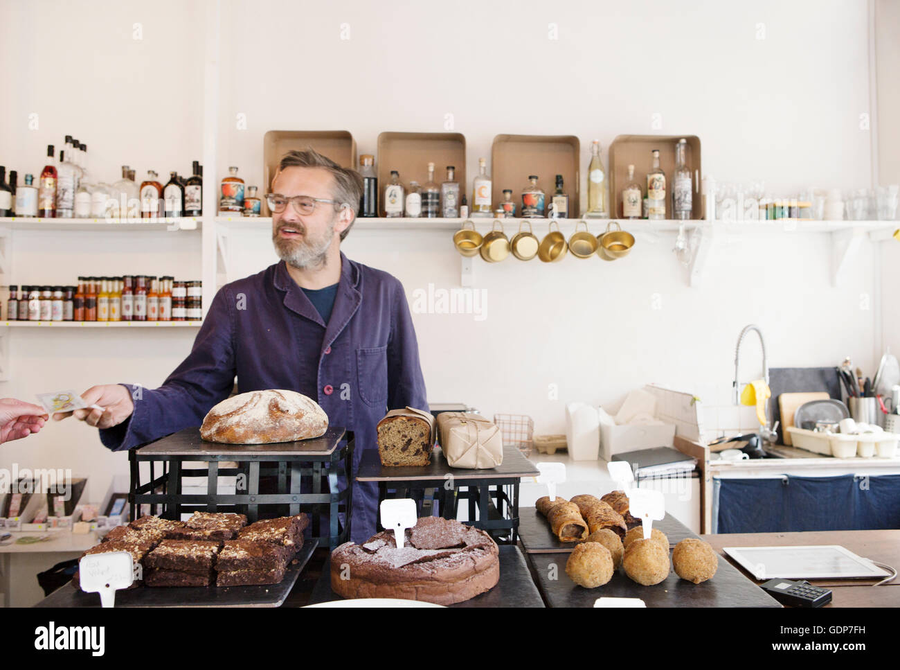 Customer handing banknote to cafe owner - Stock Image