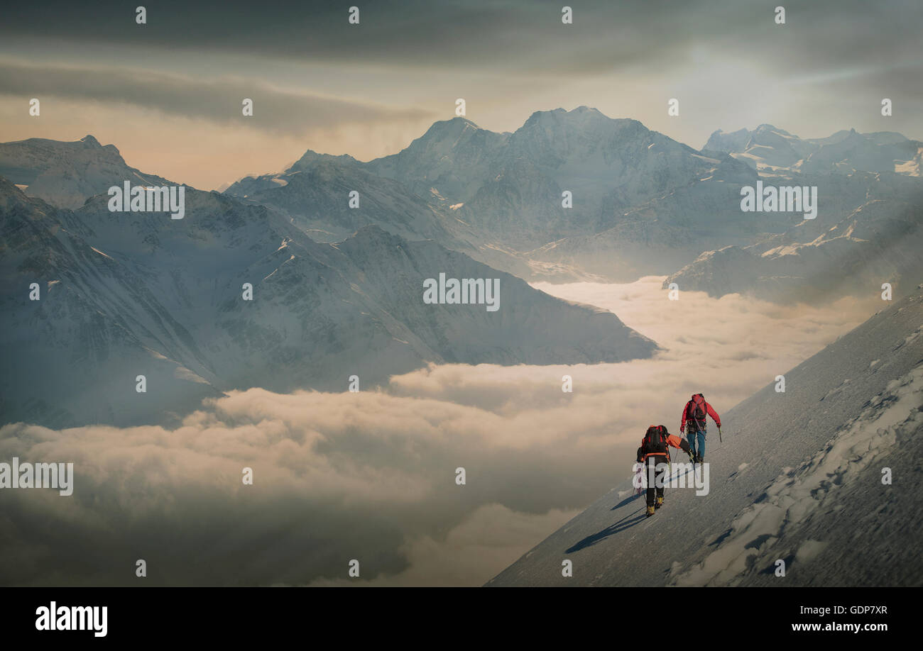 Two climbers on a snowy slope over a sea of fog in an alpine valley, Alps, Canton Wallis, Switzerland - Stock Image