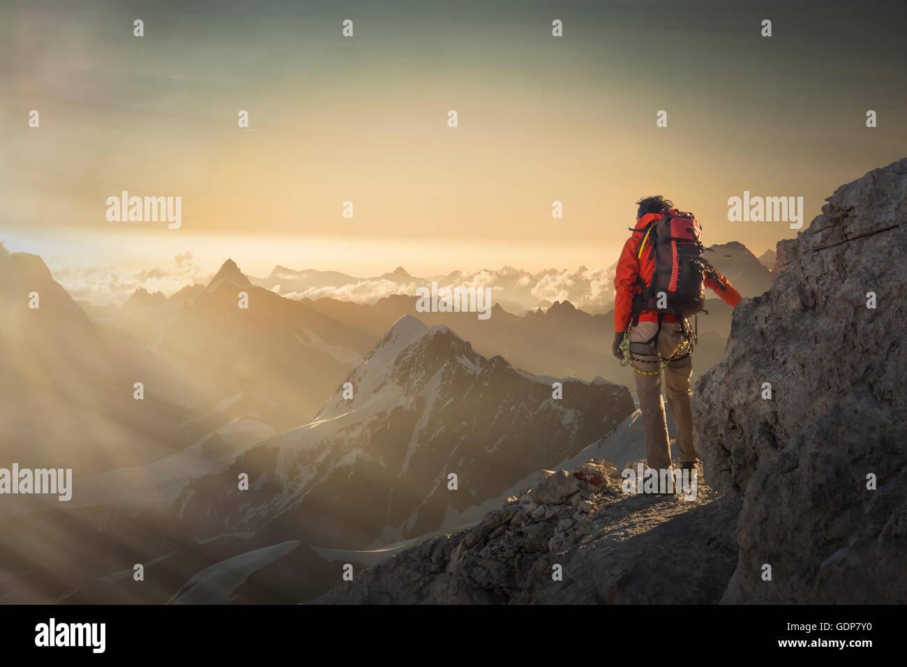 Climber watching a mountain range at sunset, Alps, Canton Wallis, Switzerland - Stock Image