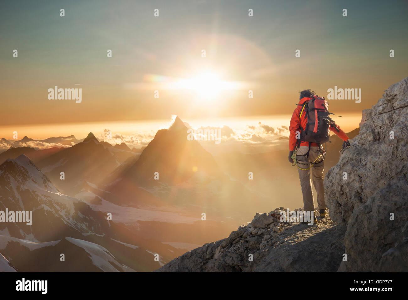 Climber watching the Matterhorn at sunset, Zermatt, Canton Wallis, Switzerland - Stock Image